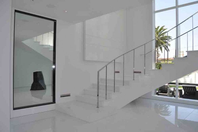 A white Thassos marble landing and entry space with thassos and lacquer curved staircase with polished metal handrail.<br />