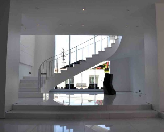 A white marble landing and entry space is made of Thassos marble. The lacquer curved staircase, has a polished metal handrail. A custom commissioned granite sculpture sits adjacent.