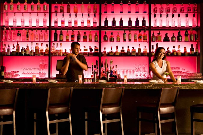 A vibrant bar with jewel tones that are backlit, adds a romantic atmosphere to a sushi restaurant in L.A.