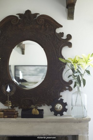 In a 1929 Spanish bungalow,  an antique limestone mantle and old carved mirror, add character.