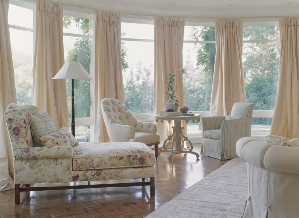 In the Pacific Palisades a dramatic round Living Room has a French linen rug from Stark.  The chaise is custom designed and covered in a large floral fabric by Clarence House.  The Rose Tarlow Nantucket Table in Gesso White flanked by two Rose Tarlow lounge chairs.  The final touch of elegance, pale peach silk drapepies buttoned onto antique distressed white rods.