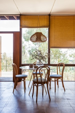 In a cantilevered modernist home nestled in the hills of Silver Lake, with sweeping views to downtown L.A. there are original cork floors throughout. Here, in the dining room, the table is from CB2, paired with vintage bentwood chairs, and a moon pendant light by Tracey Wilkinson,
