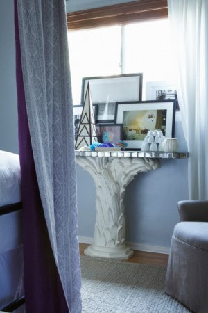 A vignette in the master bedroom displays a collection of objects and photographs on an antique console.