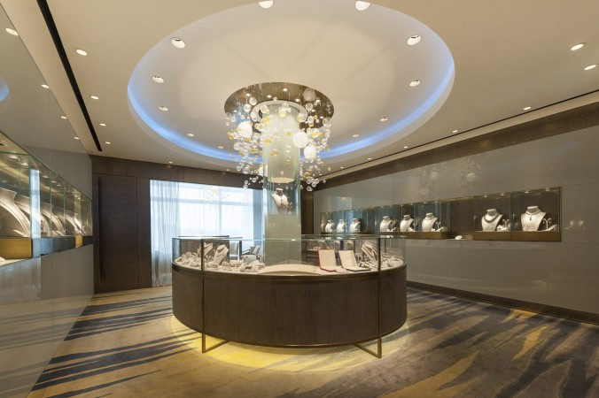 Back painted glass, mica coated wall coverings and an internally lit glass column surrounded by floating pearls create a surprising and elegant interior at  Mikimoto, in Hong Kong.