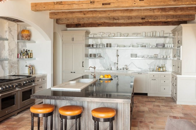 Reclaimed barn beams accent a custom kitchen featuring open zinc shelves and marble slab walls. A granite counter top from Walker Zanger crowns the wire-brushed oak island which is inset with an antique Italian sink.
