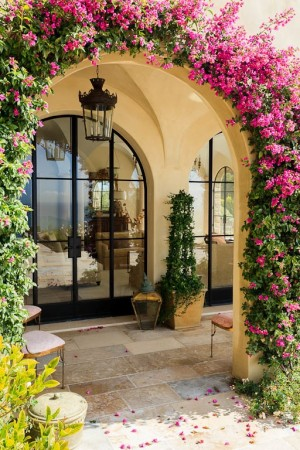 Lush bougainvillea vines grow around the arched entry to a newly built Malibu home that was designed to evoke a Tuscan farmhouse. One with repeated arched windows featuring dramatic views of the Pacific Ocean.