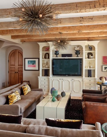 Reclaimed barn beams accent the media/family room. The room is open to the terrace.