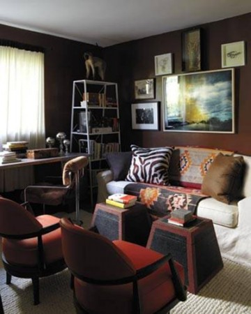 A photography collection is hung on walls painted chocolate brown above a cream covered linen sofa.  Mid-century chairs and an industrial metal desk make for a quiet library in a young couple's home.
