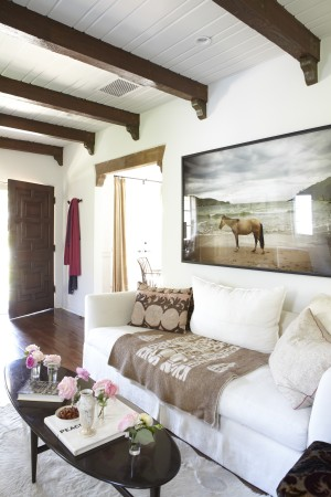 This 1929 Spanish bungalow has rustic beams, and its original oak floors. A crisp white sofa is covered with a one-of-a-kind South American blanket.