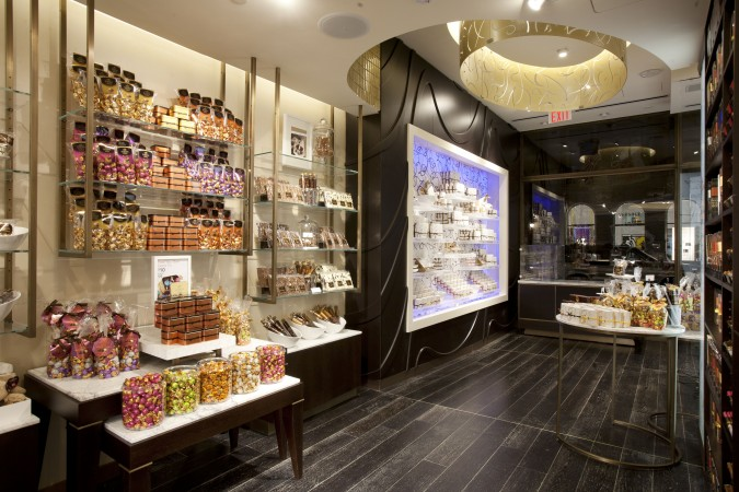At a Godiva store on 5th Avenue in New York, custom shelves are suspended from the ceiling and washed with light behind to highlight this merchandising area for grab and go items. In the background is a featured area for seasonal items with LED lights that can be custom colored in an instant.