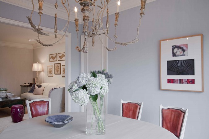 In the dining room of a Beverly Hills home, the design is in the style of Gustavian III.  The chairs are Louis XVI chairs gesso, covered in original red kid leather.  And the walls glazed and striped with tones of heather and lavender.<br />