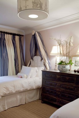 In an elegant guest dedroom  custom are covered in Bennison Chinese Toile on oyster linen.  The Danish baroque chest sits next to the bed, which has linens by Lenotine. The stuffed silk pouf with silk blue and cream stripe curtains.