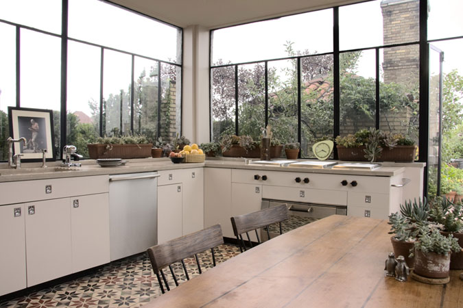 An abundance of green on the terrace that surrounds a New York City kitchen, is brought inside by  large windows, which seamlessly unite the interior and exterior. The floor has been done with vintage cement Moroccan tiles.