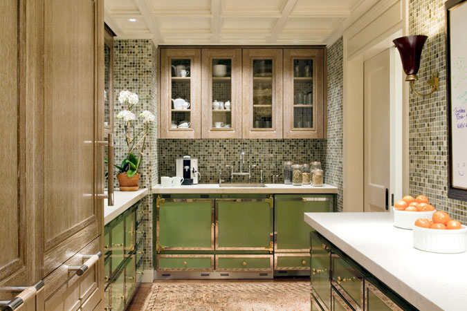 The vibrant mosaic walls and celadon green cabinets create a luxurious kitchen. The trim and level of detailing is noteworthy.