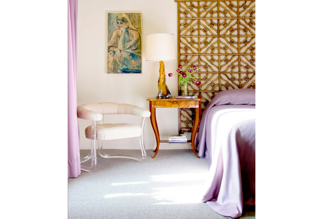 In a master bedroom, serenity is achieved through a carefully thought out mix. Including Chinese fretwork panels mounted as a headboard, a lucite chair from a Hudson NY. antique shop, and a Biedermeier side table, upon which sits a Venetian glass lamp from the 1950s.  Soft pale purple wool is draped over the bed, and is used for the curtains as well.