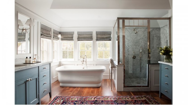 In a Brentwood, Ca. home a large bathroom features wooden floors with an antique carpet,  with furniture-like vanities, in a rich shade of blue, that have been topped with marble.The old style tub is the focal point set against a corner of windows. The large shower has large slabs of marble for the walls and a tiled floor.