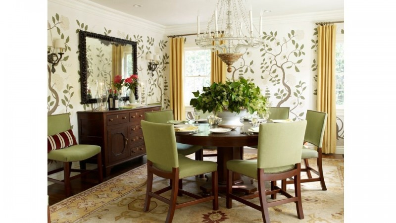 Garden motif green and white wallpaper sets the backdrop for a dining room, in a Brentwood, Ca. home, with green fabric upholstered dining chairs.
