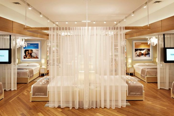 Individual pods are create for testing out the mattresses in a TempurPedic store.  Surrounded by sheer fabrics, soft music and lighting, the customer may lie down and indulge in a TempurPedic experience.