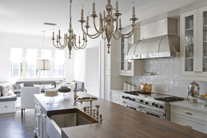 This kitchen is layered with crisp shades and textures. While light dances across the surface of the glazed tile backsplash and the gleaming stainless steel fixtures, the rubbed-oak island brings the focus to the center, where all the action is. The elegance of this project pervades the kitchen, which features silver chandeliers chosen for the candlestick-like appearance.