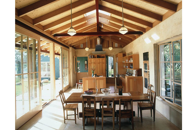In Napa County, this 2500-square foot-residence is a second home for a writer, a painter and their two young children.  A two-building scheme, linked by a covered breezeway, nestled into a 100-year-old grove of oaks, forms the general plan for the home. Sixteen-inch-thick shot-earth walls comprise the east-west portion of the living building, while the north-south walls are wood, sided inside and out with cedar.