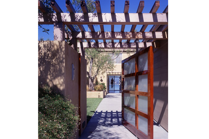 A custom designed gate leads you to an enclosed yard, where the landscape is a combination of limestone paving, lawn, and contained planting. Starting from the street, an axis leads to the house, pierces it as a two-story central hall, and continues to the bay as a dock – aligning with Mt Tamalpias across the water.