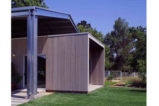 The design is rooted in the notion of radical simplicity for aesthetic effect and for budget. The house is a 20-ft by 100-ft box with a slightly sloped  metal roof for effect. This metal canopy  also links the house to the legacy of 'farm vernacular'. The house has exterior walls and a roof built from SIPS (structural insulated panels), which replaces typical 'stick framing'. This expedites construction, provides for higher insulation, and is a more sustainable way to build than typical methods.