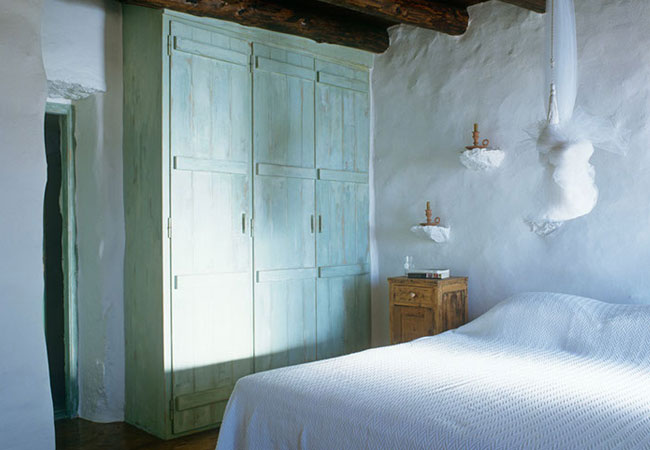 The weathered pale green painted closet doors, reminiscent of old wooden sea chests, in this bedroom with rustic beams.