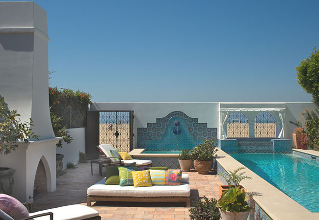 Overscaled chaise lounges have jewel toned cushions, while the vivid blue Iznik tiles match the adjacent pool.