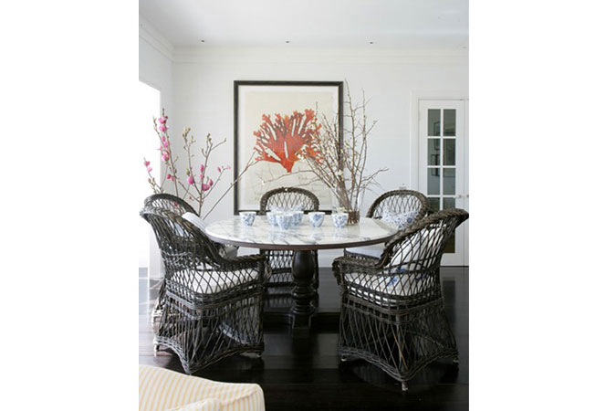 The dark wicker chairs and dark floors against the white walls of a beach house, is always classic.