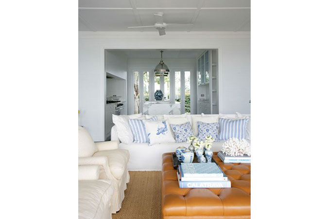The blue and white living room, with casual slip-covered sofas leads, into an open plan marble kitchen.