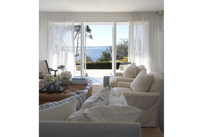The airy white room and gauze cotton curtains are set against a dramatic  sea view.