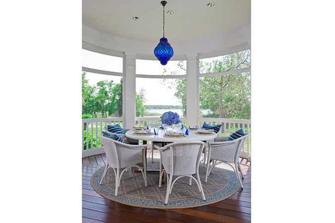 The circular folly is immersed in beachside nature, so that the sun's rays are reflected in the blue glass pendant hung above the table.