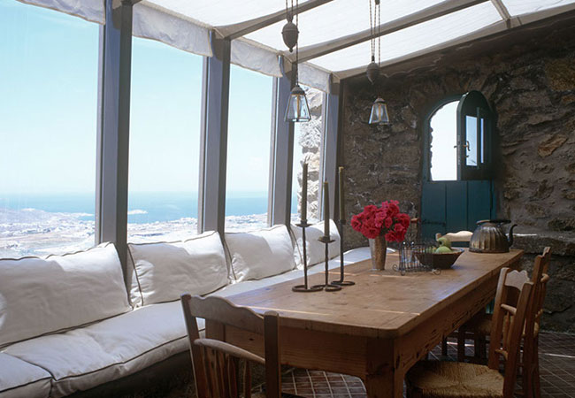 The traditional Greek rustic stone wall and table contrasts with the rectilinear conservatory windows overlooking  the Aegean Sea.