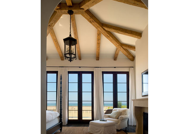 The blue of water and sky is viewed through casement French doors; while the large wooden beams give a nod to the rustic.