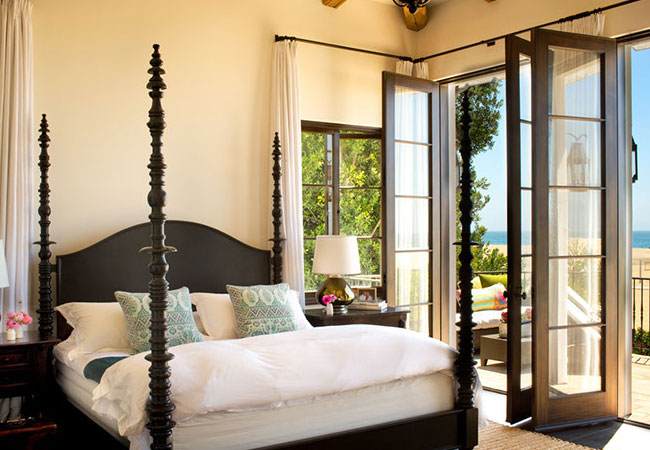 In a Spanish Colonial home on the beach in Santa Monica, the rich history of Mediterranean design is adhered to by the designer, with dark wood furniture, against pale walls; yet updated for comfort for living today. Here, original French doors open to the terrace off the bedroom.