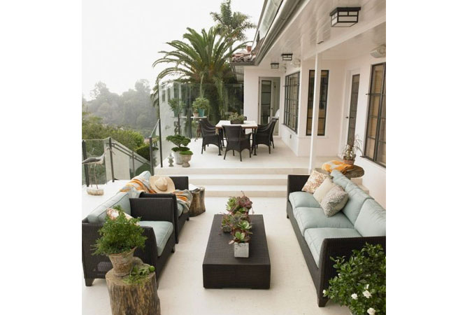 The natural wicker furniture and tree-trunk side table compliment the striking lush backdrop on a terrace in Brentwood, Ca.