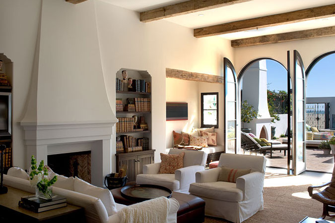The modern white sofas and airy space are juxtaposed with old wooden beams and antique leather bound books.
