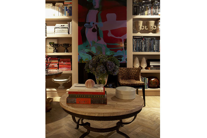 A home filled with antiques and rich detailing. The abstract painting by Dale Frank is flanked by a pair of bookcases filled with books and decorative objects. The Philippe Starck 'Mademoiselle' chair is upholstered in a chic Dolce & Gabbana leopard-print fabric. In the foreground sits a 1940s French wrought iron table with a limed oak top.