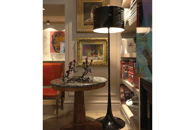 The Louis XVI-style chair is upholstered in Jim Thompson orange-red silk. Looking through to the kitchen, a Marilyn Monroe silk-screen print by Andy Warhol sits on the Carrara marble counter. The antique table is a 1830s Geridon with a black marble top and mahogany veneer base. The 'shiny black' floor lamp is the Spun Light from Flos.