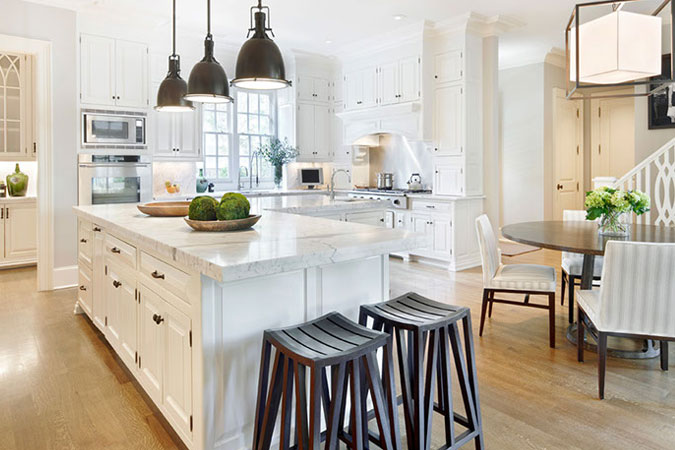 An all white kitchen is complimented by the dark wooden geometric stools in the foreground and industrial pendant lighting over the island.