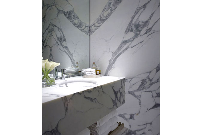 The highly patterned slabs of marble give the bathroom an almost abstract feel.
