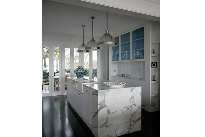 The marble kitchen, set against glass french windows, is given an element of fun through the blue glass cabinets and blue and white vase.