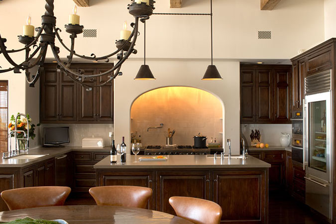 The dark wood cabinets are set against cream walls behind an elaborate iron chandelier.