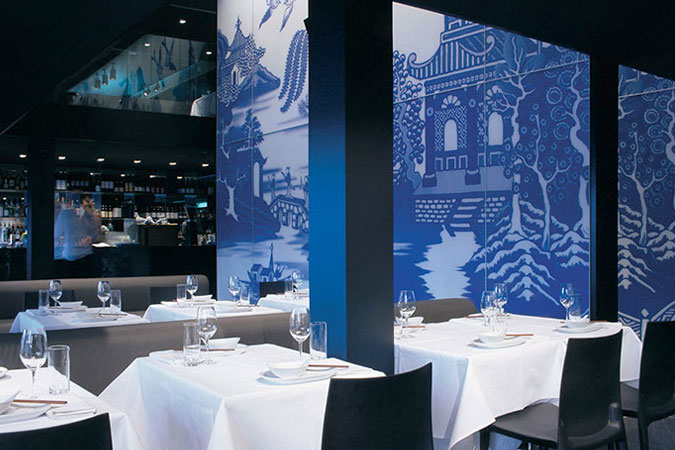 A two-level contemporary Chinese restaurant was created on Sydney's Woolloomooloo Wharf. Central to the scheme is a wall based on a blue and white porcelain 'willow' pattern and executed in graphic glass panels that form a two-story screen to conceal the stair. The remainder of the space is black glass and terrazzo.