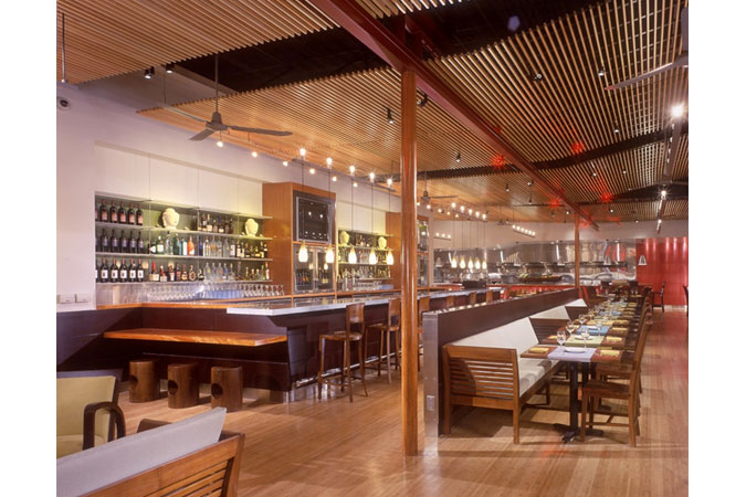 Located in San Jose, Ca., this project includes indoor-outdoor dining, an exhibition kitchen, and a bar-lounge, rendered in a style that is both modern and uniquely South-East Asian. The exhibition kitchen along the rear wall animates the deepest area of the dining room with the action of the chefs against a vivid backdrop of red anodized aluminum panels.