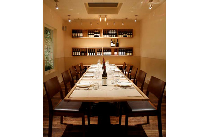 "Terzo&#039;s ""wine room,"" offers regular seating and a setting for private parties of 20.  Wall cabinets of wine and Edison light bulbs continue the warm look of the dining room. A large, vertical window on the south side of the room gives diners a close-up view of the olive tree planted outside.<br />"