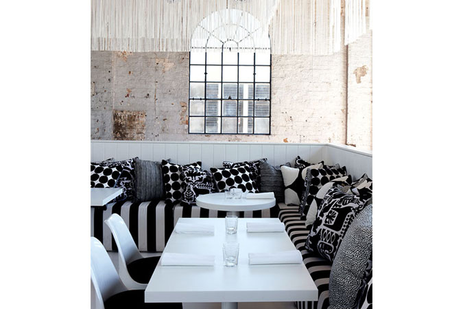 "Canteen is a restaurant bringing fresh, effortless dining to CarriageWorks, a restored railway workshop in Sydney's Eveleigh area. The goal was an ambience of accessible glamour, with an interior not typical of current fashion. The scale, rusticity and antiquity of the space determined the design approach. The result is an inviting white oasis within the industrial setting. The main dining area sits stage-like on a raised podium with a banquette surround, mirrored above by a box truss holding stage lights fringed, theatre style, with slit drapes, creating a form of ""vertical containment"" and a sense of intimacy. <br />