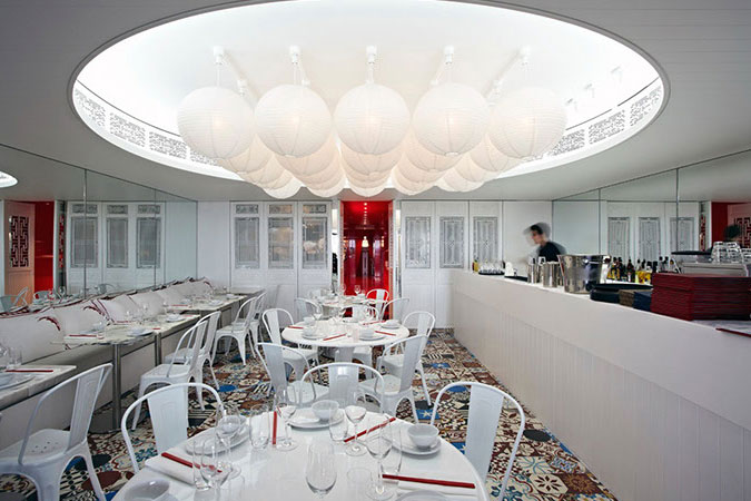 China Beach in Sydney, Australia, is light and fresh, in keeping with its beachside location. Its interior fuses 'white on white' timber-lined walls and ceilings with a vivid pattern in the form of a Vietnamese stenciled concrete patchwork tiled floor. A series of whitewashed vintage Chinese screens allows views through to the kitchen and whitewashed vintage furniture mixes with classic white French café chairs and molded plastic models. <br />
