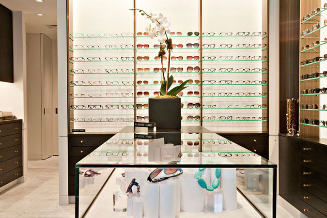 For a simple, yet casually elegant eye glass shop in New York City, custom made display cases were  inspired by mid-century modern look. The floor is white Carrera marble. The back wall becomes an interesting graphic element at the same time is is the display for glasses. It's made of glass, which has been backlit and has burnished bronze trim.