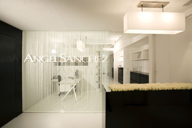 A  New York City showroom for a high end fashion designer uses black and white to accent the designer's work. Windows are covered with woven black shades and all wood work has been stained white.
